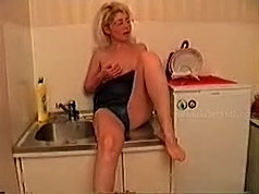 Older housewife gets horny while cooking dinner in the kitchen