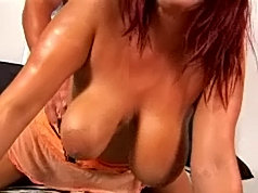 Redhead gets naughty and oils up her pillowy bosom for some hardcore fun