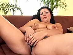Raven-haired older hottie masturbates on the couch with her favorite vibrator