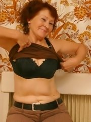 Old redhead granny came into porn studio to act in porn and now shows her body