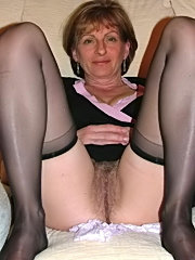Hot milf in stockings plays with her tits and pussy, then gets double-teamed on a leather sofa
